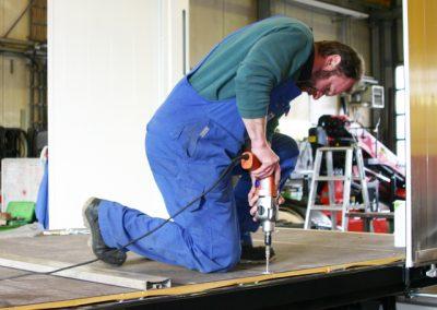 Mitarbeiter Grimm und Partner Fahrzeugbau in der LKW Werkstatt Suhl beim Bohren und Reparieren eines LKWs